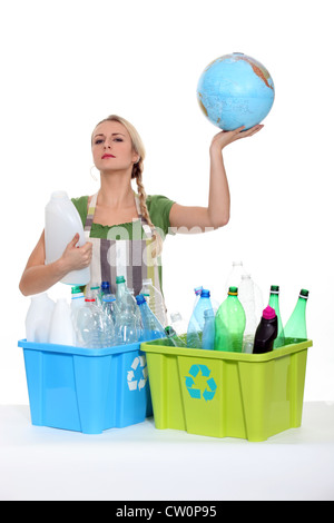 Woman recycling and holding planet earth in her hands - Stock Photo
