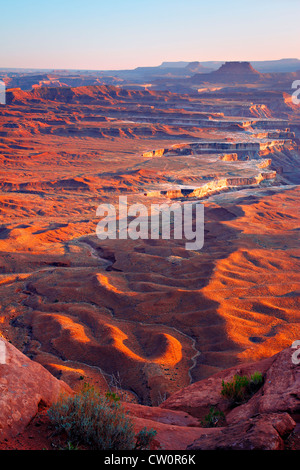 rugged desert terrain in afternoon light cliffs and mesas  in background.  elevated viewpoint portrait orientation - Stock Photo