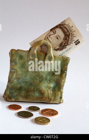 Money bag - £10 note showing Queen's head in pottery bag with coins spread around isolated on white background - Stock Photo