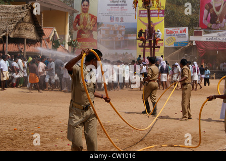 Fire Force Workers Sprinkling Water on the Hot Sand on the Temple Pathways to help in Garudan thookkam ritual at - Stock Photo