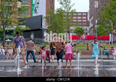 People cooling down their feet in the water sprays at Place des festivals in downtown Montreal, province of Quebec, - Stock Photo