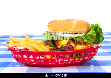 A freshly grilled cheeseburger in a red basket with freshly cooked french fries. - Stock Photo