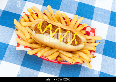 A chilidog with mustard in a basket of fresh French fries on a blue and white checkered tablecloth. - Stock Photo