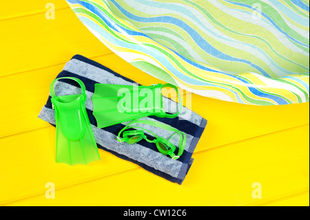 Swim flippers and eye goggles on a beach towel next to a plastic youth swimming pool. - Stock Photo