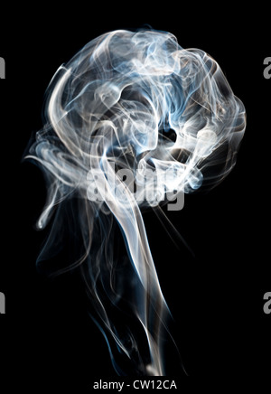 A plume of cigarette smoke against a black background. - Stock Photo