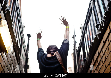 Manchester, UK - 4 August 2012: a young woman raises her arms to the sky exiting a pub in a basement. - Stock Photo