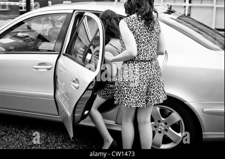 Manchester, UK - 4 August 2012: two leopardskin dressed girls get into a cab getting ready for a night out. - Stock Photo