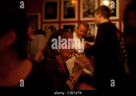 Manchester, UK - 4 August 2012: a senior woman sips her drink while listening to live music at the Matt & Phreds - Stock Photo