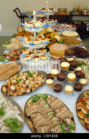 Cakes, smoked salmon sandwiches,scones (with jam & clotted cream), pork pies, and muffins, on the buffet table at - Stock Photo