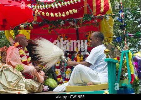 A Hare Krishna practioner fans a statue of Lord Jaqannatha (Ratha Yatra) - Stock Photo