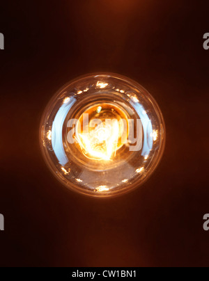 Single lit up incandescent tungsten light bulb isolated on black background - Stock Photo