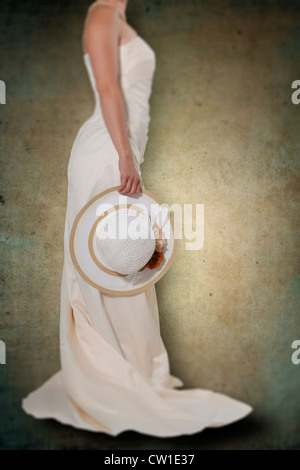 a woman in a white dress with a straw hat - Stock Photo