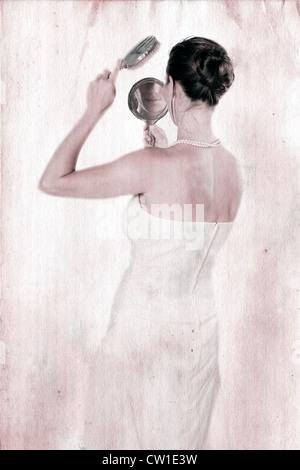 eine hübsche Frau betrachtet sich in einem antiken Handspiegel und bürstet sich die Haare - Stock Photo