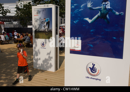 A young boy eats an ice cream below portraits of the BMX athlete Shanaze Reade and celebrated diver Tom Daley, both - Stock Photo