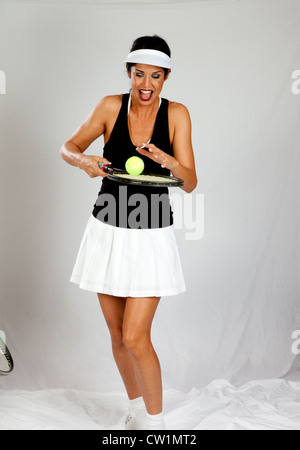 Lovely mature woman wearing a tennis skirt and top, playing with a tennis racket and ball, smiling with joy and - Stock Photo