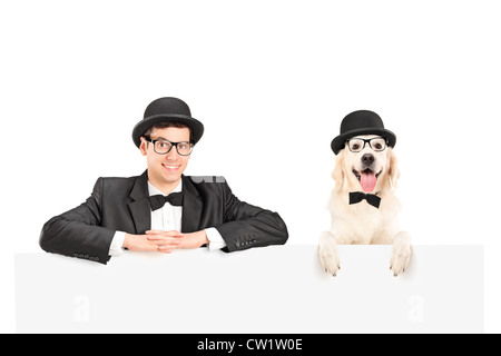 Man and dog with bow tie and hats posing behind white panel - Stock Photo