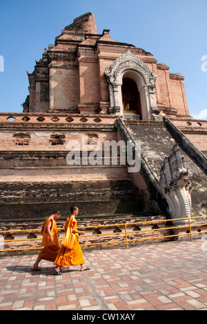 Two monks walking in front of Wat Chedi Luang, Chiang Mai, Thailand - Stock Photo
