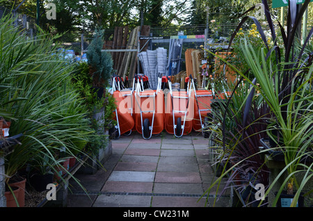 Stack of orange wheelbarrows in garden centre and row of plants - Stock Photo