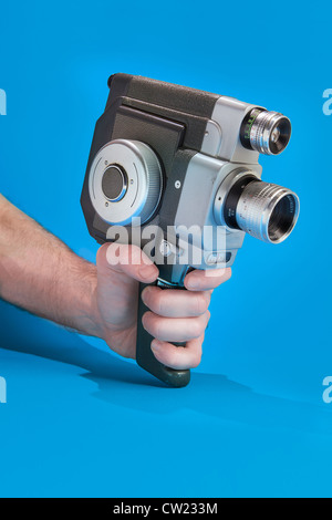 A man's hand holding an old fashioned 8mm film camera - Stock Photo