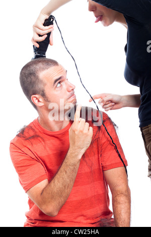 Funny hairdresser shaving man with hair trimmer, isolated on white background. - Stock Photo