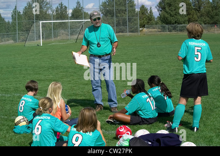 The male coach gives a pep talk while a young girls' team rests on the playing field between after-school soccer - Stock Photo