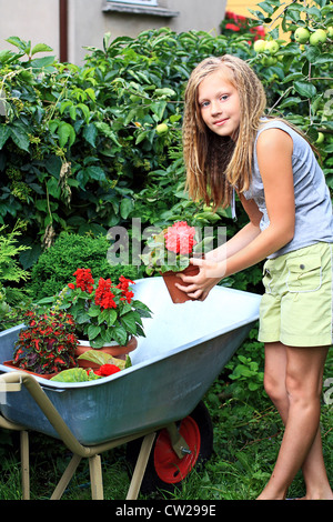 A 12 years old girl in the garden with flowers and wheelbarrow - Stock Photo