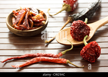 Assortment of dried chili peppers on wooden mat - Stock Photo