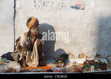 Elderly street-side vendor who sells trinkets on the look out for potential customers - Pushkar, Rajasthan, India - Stock Photo