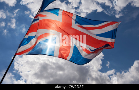 Union jack flag flying against a blue sky with some cumulus clouds. The sun is shining through the flag. - Stock Photo