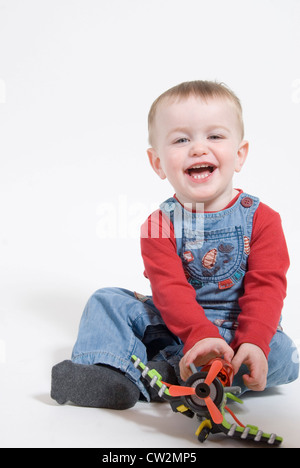 Little Boy Sitting and Laughing, Playing with Toy Airplane, Studio Portrait Cut Out on White - Stock Photo