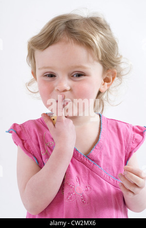 Sshhhhhh! Cute Little Girl Holding up finger to her mouth in Shushing Gesture, Studio Portrait Isolated on White