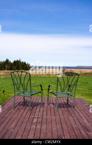 Two deck chairs sit on a wooden deck overlooking an ocean view - Stock Photo