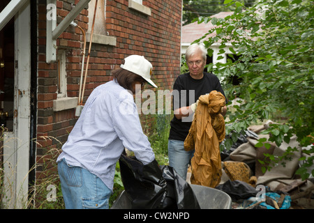 Detroit, Michigan - Members of the Three Mile Block Club cut weeds and remove illegally-dumped trash at an abandoned - Stock Photo