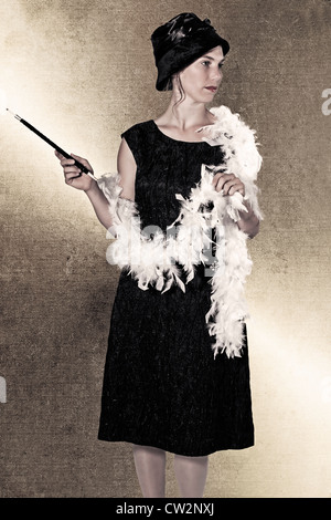 a woman in a black dress with a feather boa and cigarette holder - Stock Photo