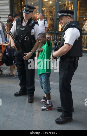 London Olympics young boy poses for photograph with two British armed policeman on duty at th e Olympics HOMER SYKES - Stock Photo