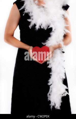 a woman in a black dress with a feather boa holds a red heart in hands - Stock Photo