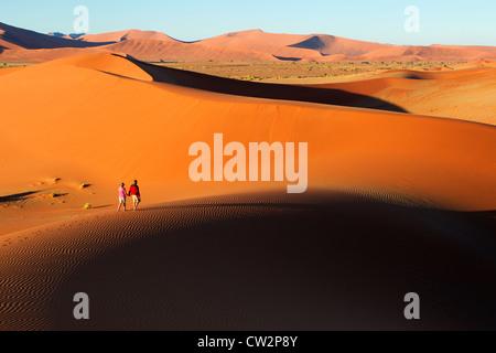 Couple walking along edge of sand dunes,Soussvlei,Namibia. - Stock Photo