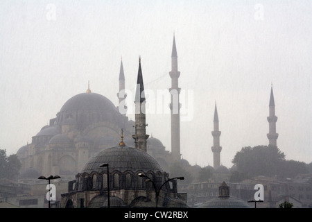 The top roofs domes of the new mosque Yeni camii Istanbul under heavy rein Turkey - Stock Photo