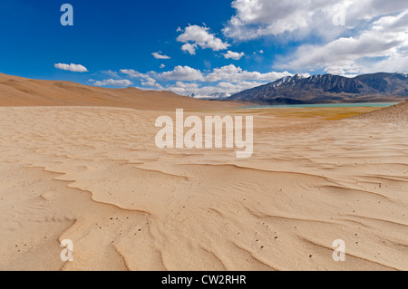 Wave-like patterns in the sand caused by the wind, a lake and mountains in the distance, blue sky, white clouds - Stock Photo
