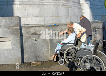 Collecting Lourdes spring water from the Sanctuary of our Lady of Lourdes ,Haute-Pyrenees, France - Stock Photo