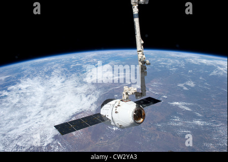 SpaceX Dragon commercial cargo craft grappled by the Canadarm2 robotic arm at the International Space Station Earth - Stock Photo