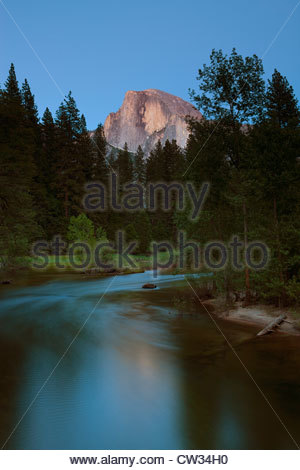 Half Dome, turned red by the twilight glow, towers over the Merced River in Yosemite National Park, California. - Stock Photo