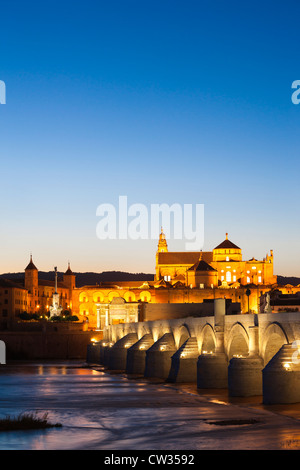 Cordoba Spain. Great, Grand Mosque, Mezquita and Cathedral with Roman Bridge on Guadalquivir river at dusk.  Andalusia - Stock Photo