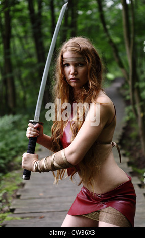 portrait of young woman with sword at forest - Stock Photo