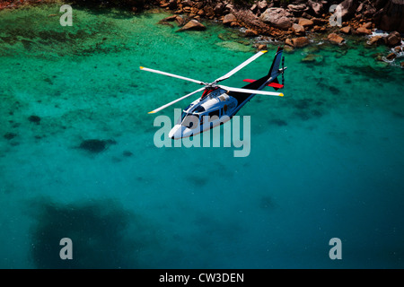 Agusta 109C Helicopter flying over the coast of Praslin.Seychelles - Stock Photo