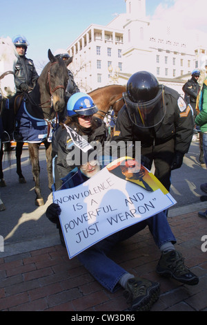 US Park Police clear the streets of a sitting protester wearing a sign reading 'Nonviolence is a Powerful and Just - Stock Photo