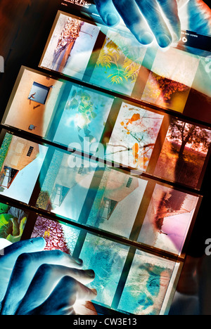 Photographer looks at a sheet of slides - digitally manipulated image - Stock Photo
