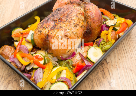 A ready to eat freshly roasted chicken in an oven dish with roasted vegetables - studio shot - Stock Photo