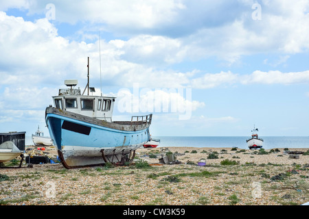 Working fishing boats pulled up onto the beach at Dungeness, Kent, UK - Stock Photo