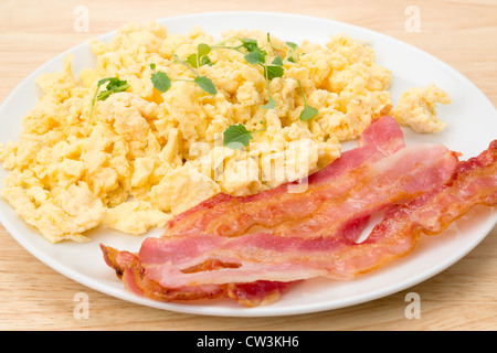 Scrambled eggs with streaky bacon breakfast - studio shot - Stock Photo